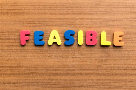 feasible: feasible  colorful word on the wooden background