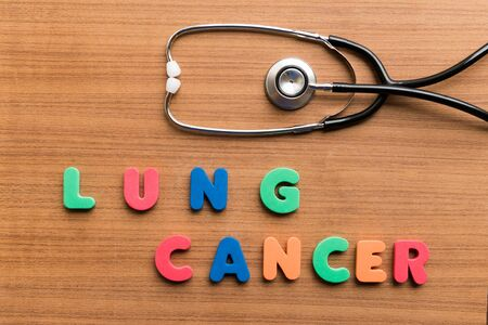 lung cancer: lung cancer  colorful word with stethoscope on wooden background Stock Photo