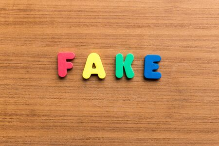 fake money: fake  colorful word on the wooden background