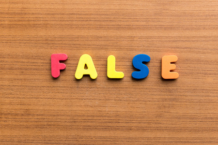 false: false  colorful word on the wooden background