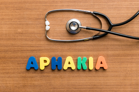crystalline lens: Aphakia  colorful word with Stethoscope on wooden background