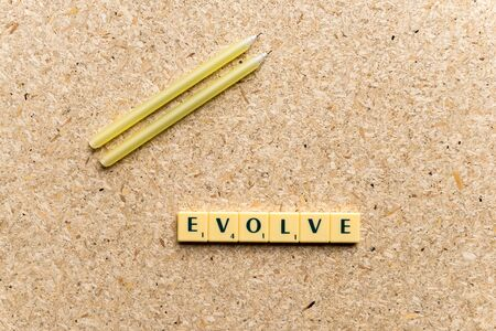 evolve: evolve  word on the simple  wooden background