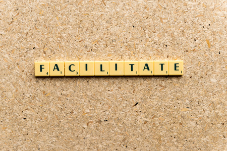 facilitate: facilitate  word on the simple  wooden background Stock Photo