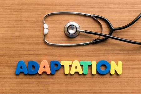 adaptation: Adaptation  colorful word with Stethoscope on wooden background Stock Photo