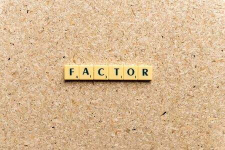 factor word on the simple wooden background