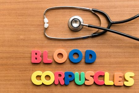 corpuscles: Blood corpuscles   colorful word with Stethoscope on wooden background Stock Photo