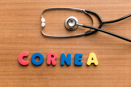 cornea: Cornea   colorful word with Stethoscope on wooden background