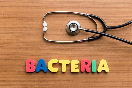 unicellular: Batteri parola colorato con stetoscopio su fondo in legno