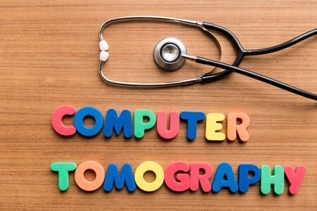 tomography: Computer tomography   colorful word with Stethoscope on wooden background