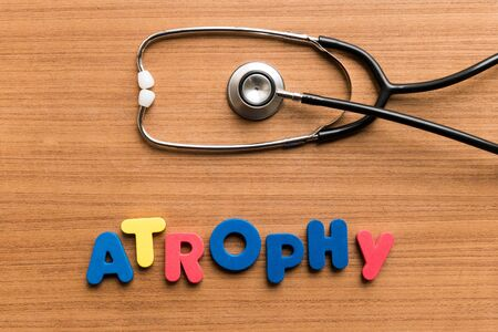 wasting away: Atrophy   colorful word with Stethoscope on wooden background