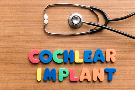 Cochlear implant   colorful word with Stethoscope on wooden background