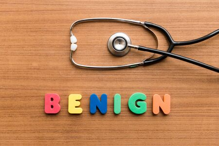 benign: Benign   colorful word with Stethoscope on wooden background Stock Photo