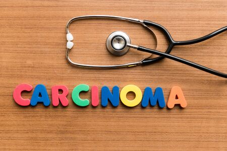carcinoma: Carcinoma   colorful word with Stethoscope on wooden background Stock Photo