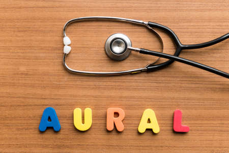 aural: Aural   colorful word with Stethoscope on wooden background