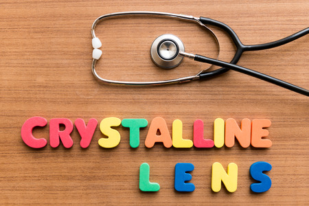 crystalline lens: Crystalline lens   colorful word with Stethoscope on wooden background Stock Photo
