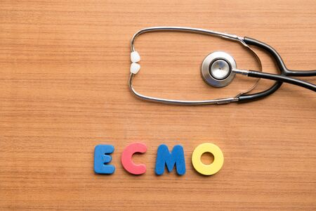 ECMO (extracorporeal membrane oxygenation) colorful word with stethoscope on the wooden background Standard-Bild