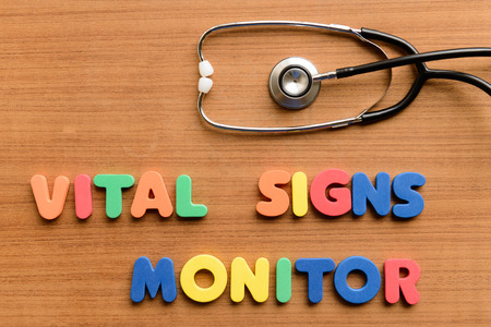 Vital signs monitor  colorful word on the wooden background