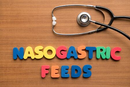 feeds: Nasogastric feeds (NG feeds) colorful word with stethoscope on the wooden background