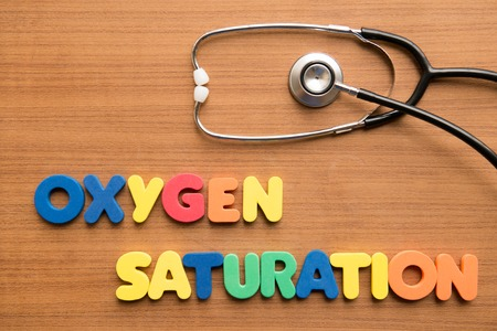 saturation: Oxygen saturation colorful word with stethoscope on the wooden background