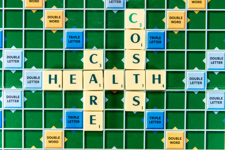 health care costs: June 19, 2015: Dhaka, Bangladesh - health care costs Crossword on the colorful game board