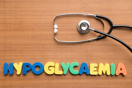 hypoglycaemia: Hypoglycaemia colorful word with stethoscope on the wooden background Stock Photo