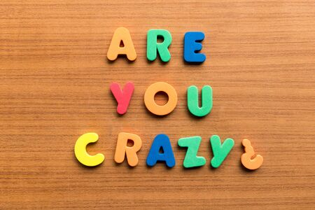 positiveness: are you crazy  colorful words on the wooden background