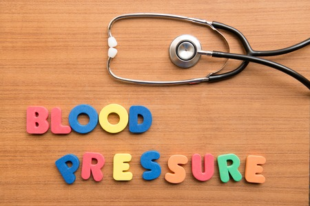 monitored: Blood pressure colorful word with stethoscope on the wooden background Stock Photo