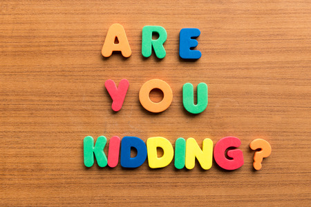 carved letters: are you kidding  colorful words on the wooden background