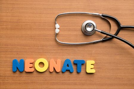 neonate: Neonate colorful word with stethoscope on the wooden background