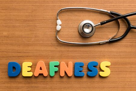 deafness: deafness  colorful medical word and stethoscope on the wooden background