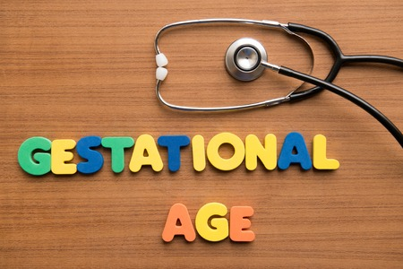 gestation: Gestational age colorful word with stethoscope on the wooden background Stock Photo