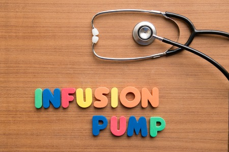 syringe pump: Infusion pump colorful word with stethoscope on the wooden background