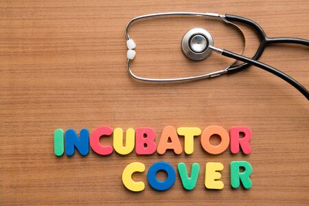 Incubator cover colorful word with stethoscope on the wooden background