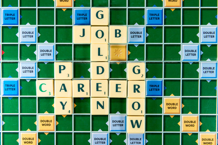 careerist: June 19, 2015: Dhaka, Bangladesh - golden job carrer pay grow Crossword on the colorful game board