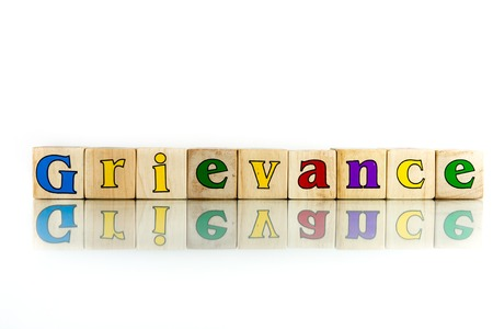 grievance: grievance colorful wooden word block on the white background