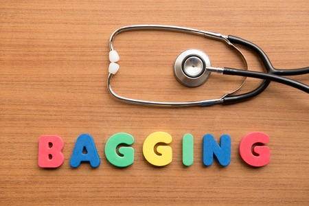 bagging: Bagging colorful word with stethoscope on the wooden background Stock Photo