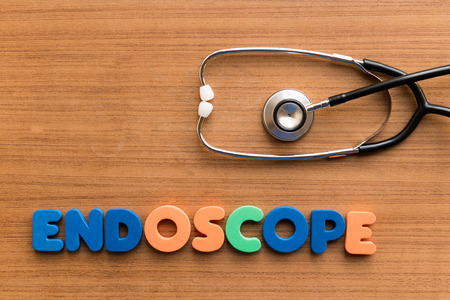 endoscope: endoscope  colorful medical word and stethoscope on the wooden background