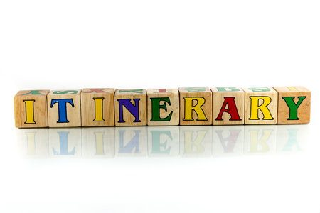 itinerary: itinerary colorful wooden word block on the white background