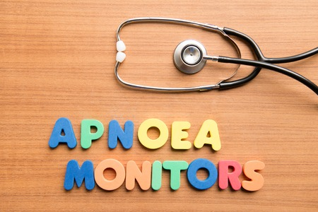 medical ventilator: Apnoea monitors colorful word with stethoscope on the wooden background