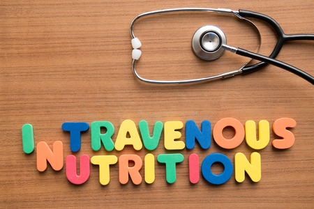 Intravenous (IV) nutrition colorful word with stethoscope on the wooden background