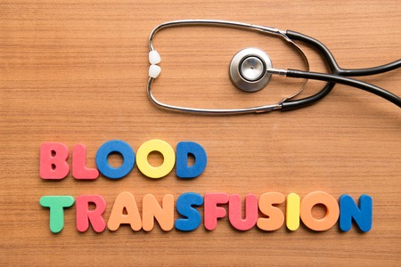 transfusion: Blood transfusion colorful word with stethoscope on the wooden background Stock Photo