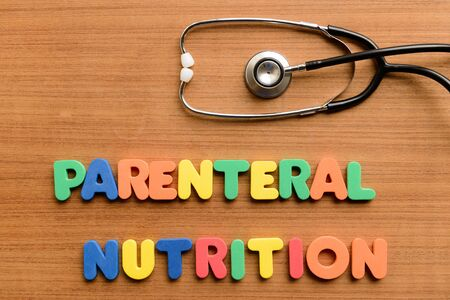 parenteral: Parenteral nutrition colorful word on the wooden background Stock Photo