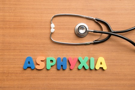 in somnolence: asphyxia colorful word with stethoscope on the wooden background Stock Photo