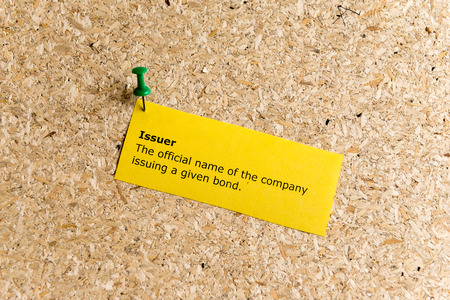 issuer: issuer word typed on a paper and pinned to a cork notice board