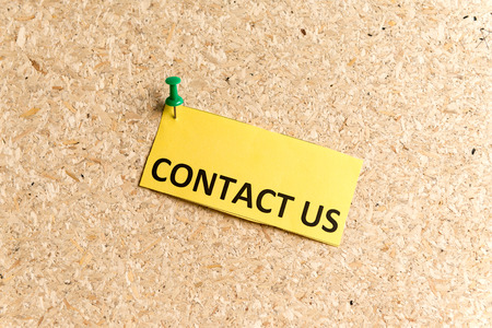 contact us: contact us word typed on a paper and pinned to a cork notice board