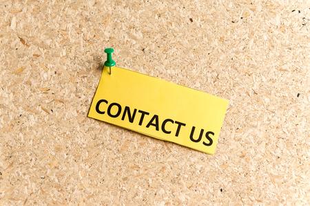 Kontaktieren Sie uns Wort getippt auf dem Papier und auf ein Korken-Informationstafel festgesteckt Standard-Bild - 46294477