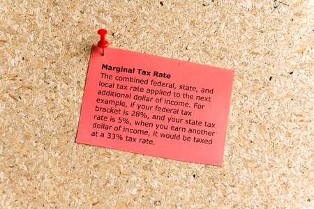marginal: marginal tax rate word typed on a paper and pinned to a cork notice board