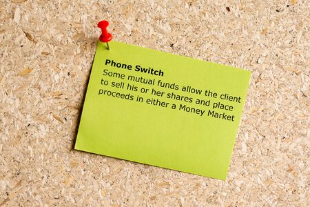 sell shares: phone switch word typed on a paper and pinned to a cork notice board
