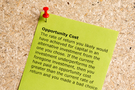 opportunity cost word typed on a paper and pinned to a cork notice board Standard-Bild