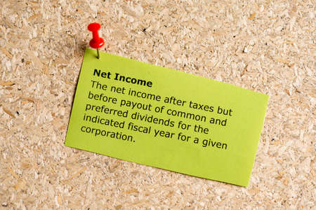 net income: net income word typed on a paper and pinned to a cork notice board